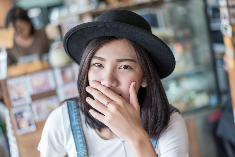 girl covers her mouth with her hands after passing gas