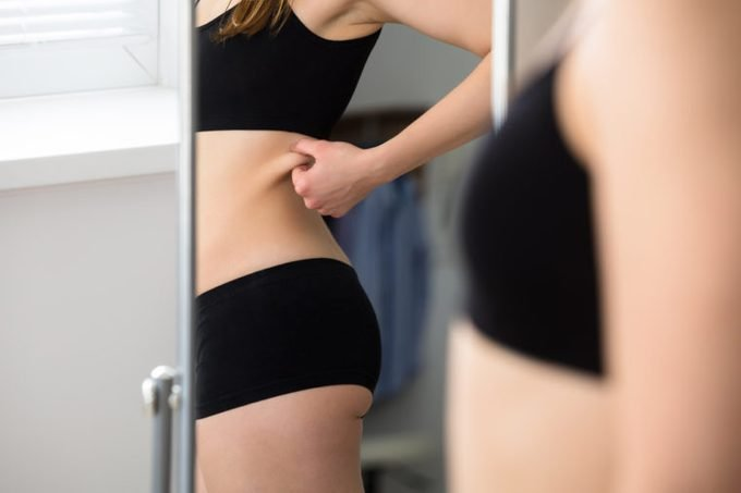 Reflection Of A Woman Pinching Belly Skin In Mirror