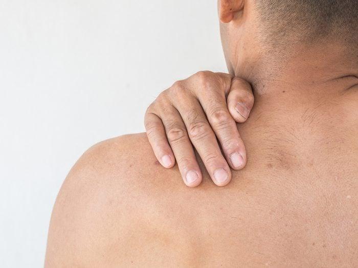 man massaging shoulder, back pain