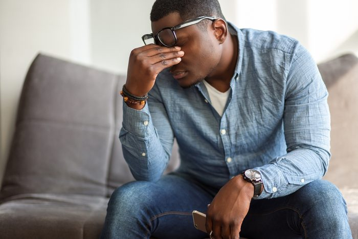 man massaging bridge of his nose with his eyes closed