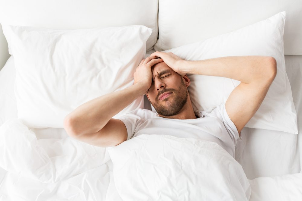 man lying in bed with headache