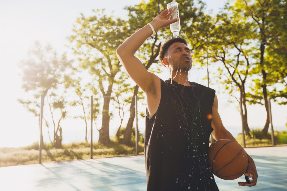 young man spilling water on himself after training, basketball game, tired player, hot summer day