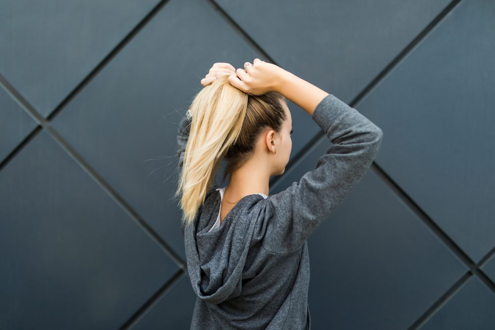 woman putting her hair into a ponytail