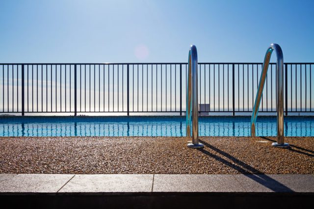 Swimming pool edge with ladder, fence and sky background