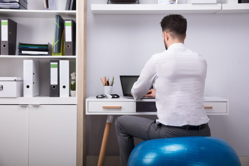 Businessman Sitting On Fitness Ball Using Laptop