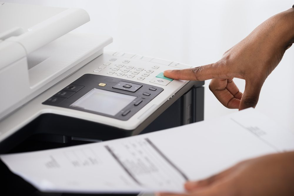 Close-up Of Young Businesswoman Hand Operating Printer In Office