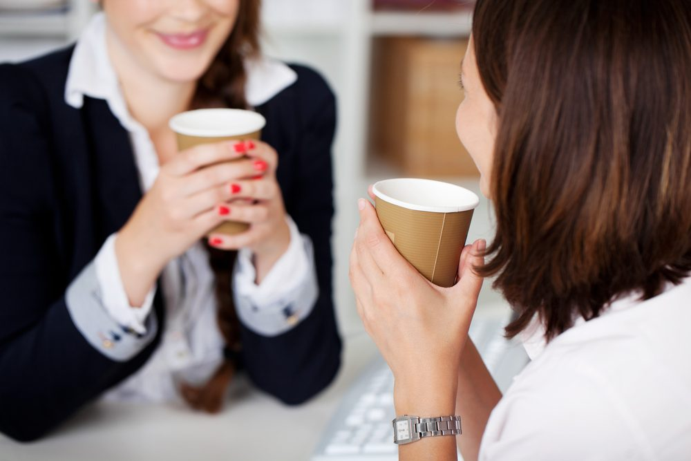 Office coffee break with two female colleagues sitting chatting over cups of coffee