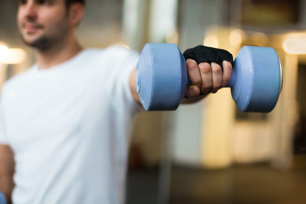 sport and recreation concept - sporty men hands with light blue dumbbells