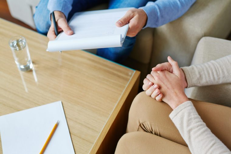 male therapist with note pad talking to woman with hands clasped