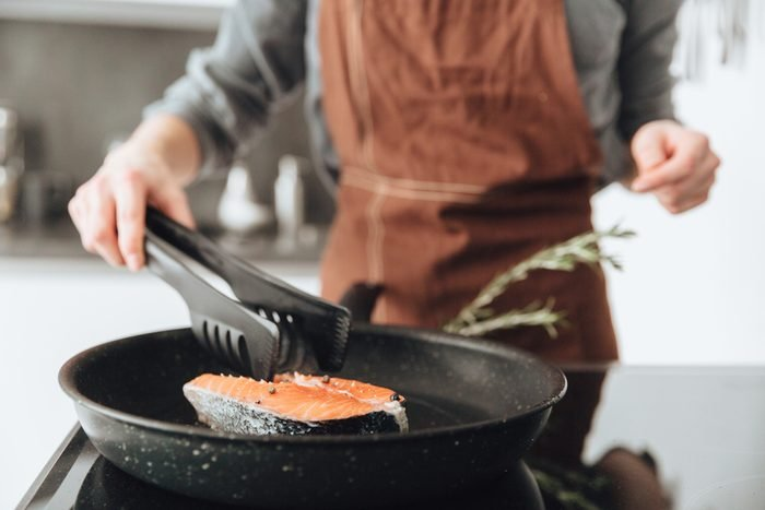 Cropped image of young lady standing in kitchen while cooking salmon.