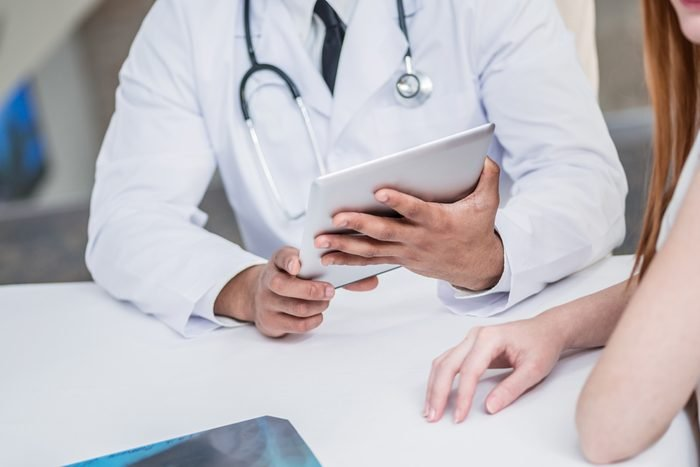 Doctor holding tablet and talking with a patient in the hospital.