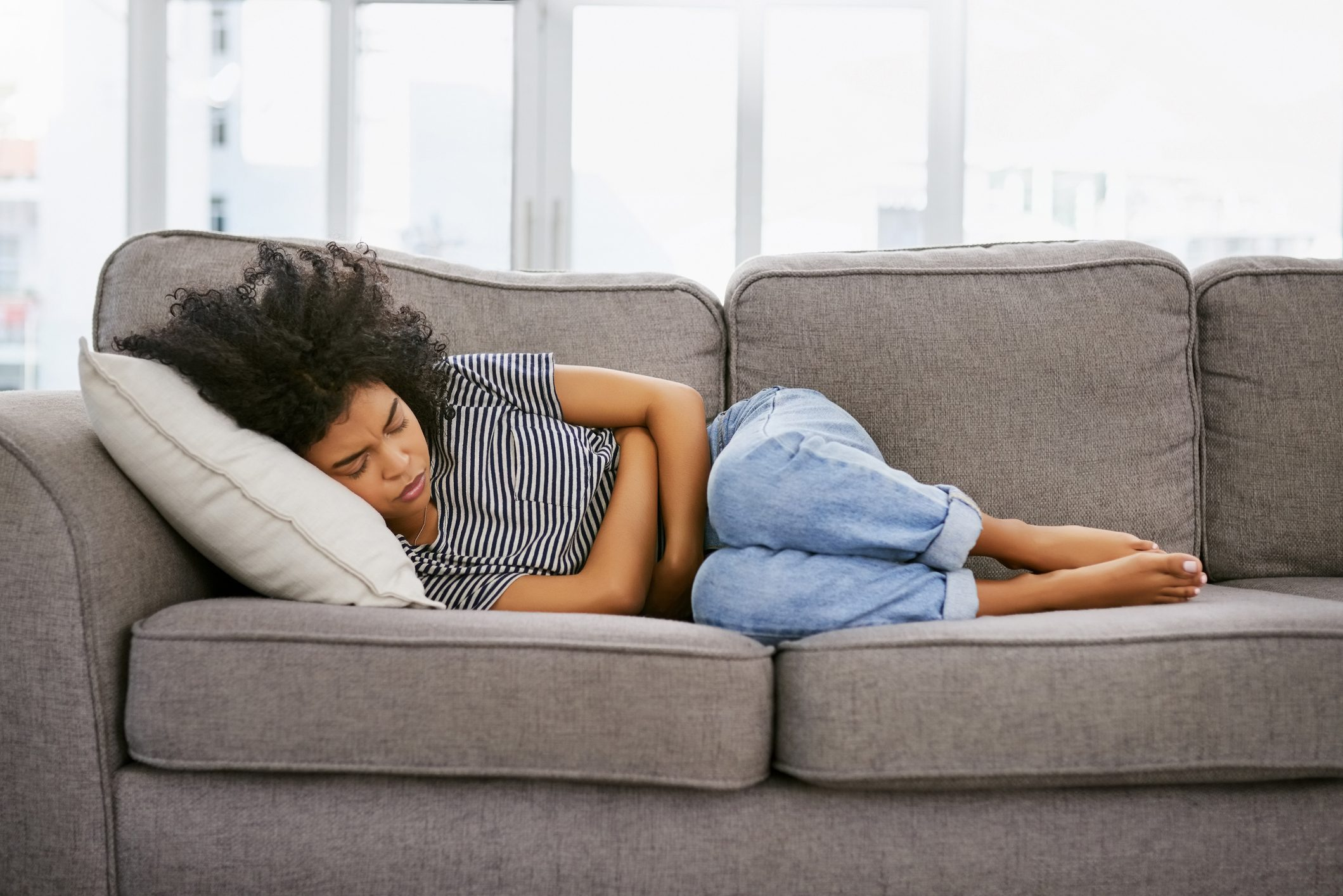 woman laying on couch with stomach ache