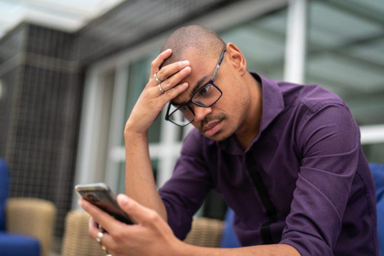 young man upset looking at his phone
