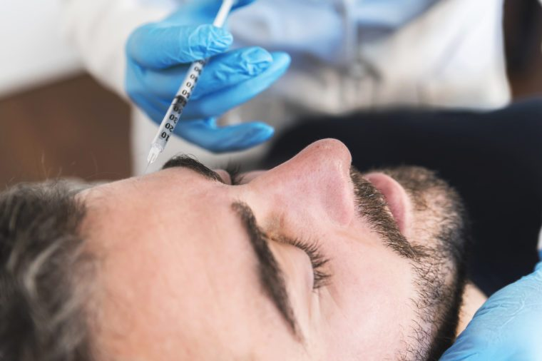 Close up of man at clinic receiving injection fillers on forehead. botox needle