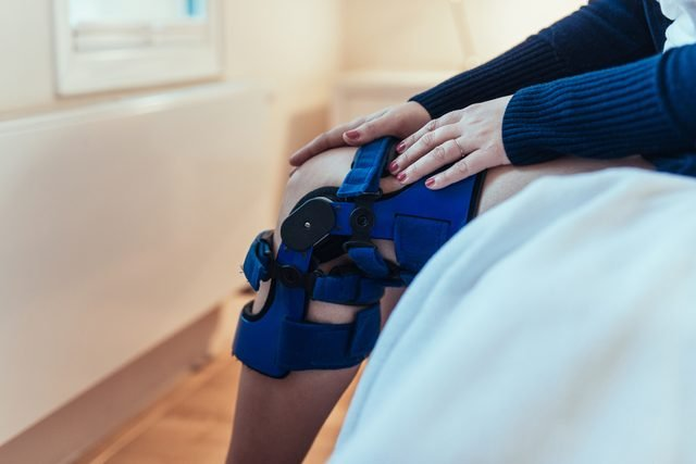 woman with knee brace sitting on bed resting
