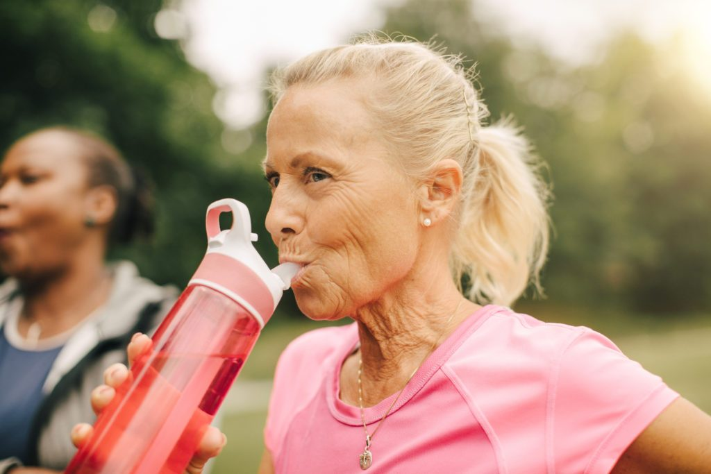woman drinking water from water bottle outside while exercising