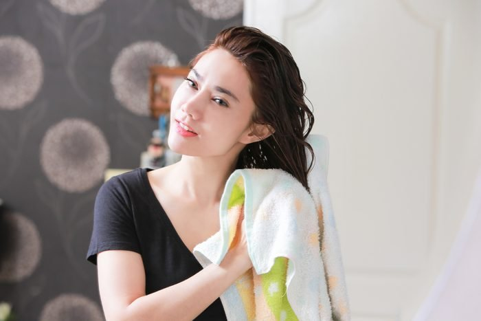 woman drying hair with towel