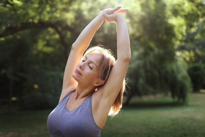woman outside exercising and stretching arms above head
