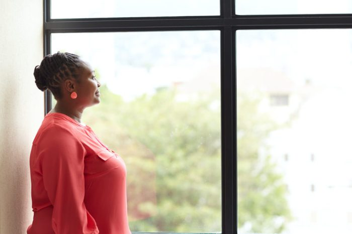 woman looking out the window thinking and taking a deep breath