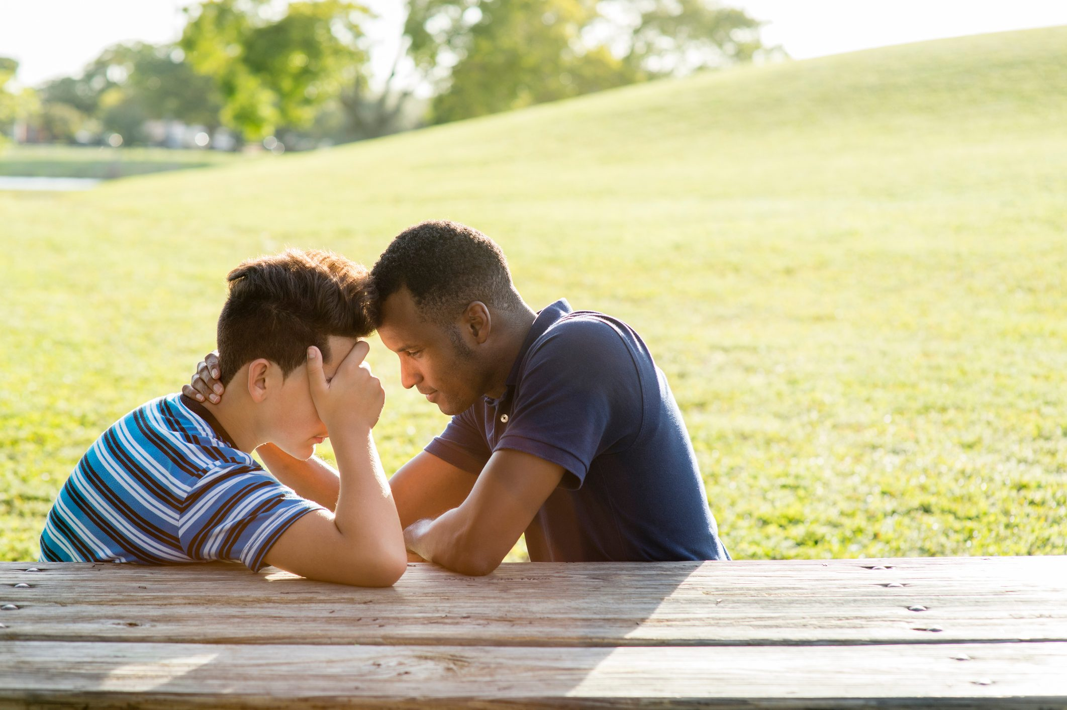 two young med talking at a picnic table in the park
