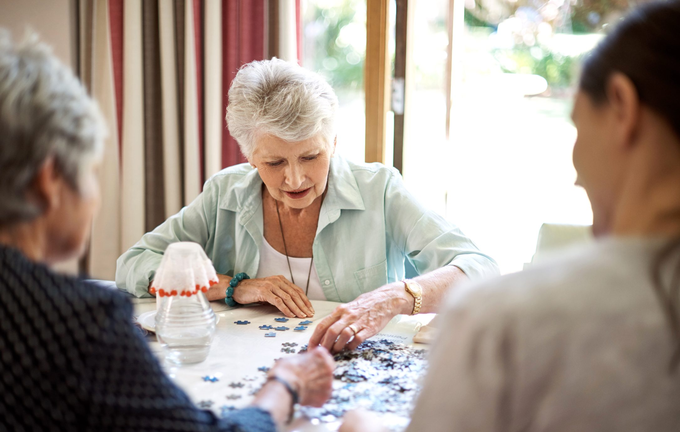 group of senior women working on a puzzle