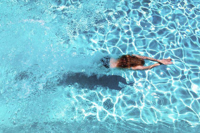 overhead shot of woman swimming in pool