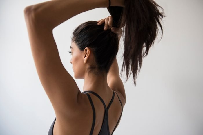 woman putting her hair into ponytail