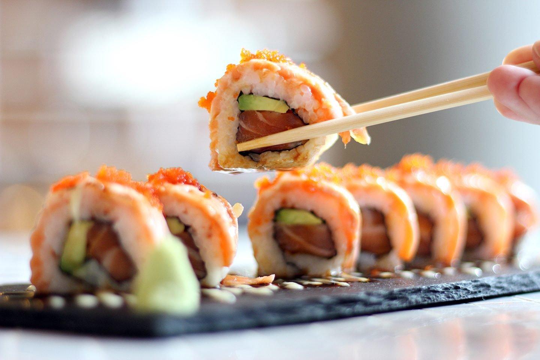 close up of sushi in chopsticks