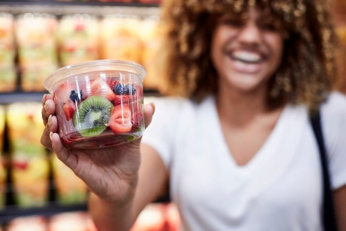 woman holding cup of fruit salad in grocery store