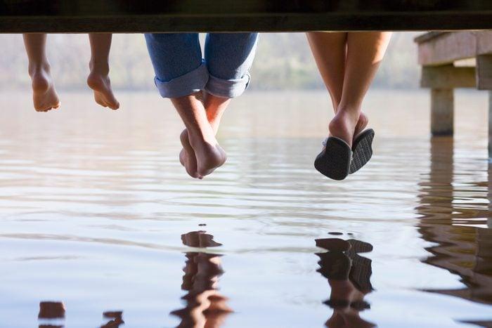 feet hanging off of dock