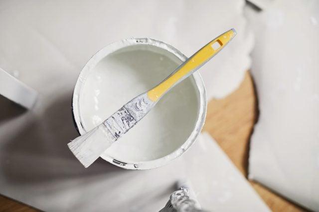 overhead shot of open paint bucket with paintbrush