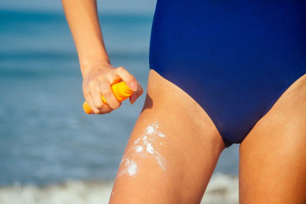 woman spraying sunscreen on her legs