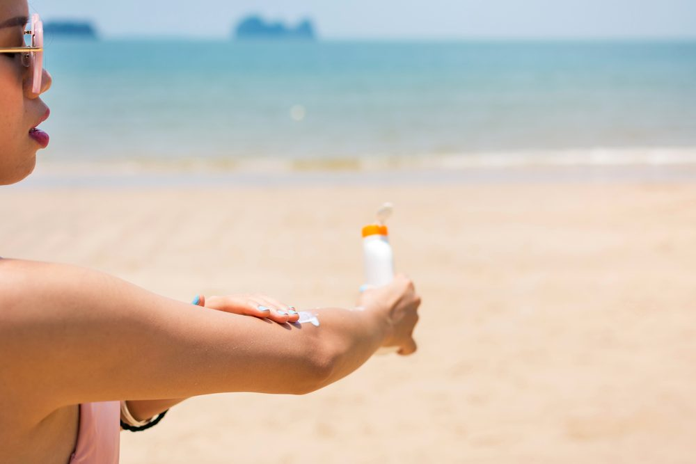 woman applying sunscreen on her arm at the beach