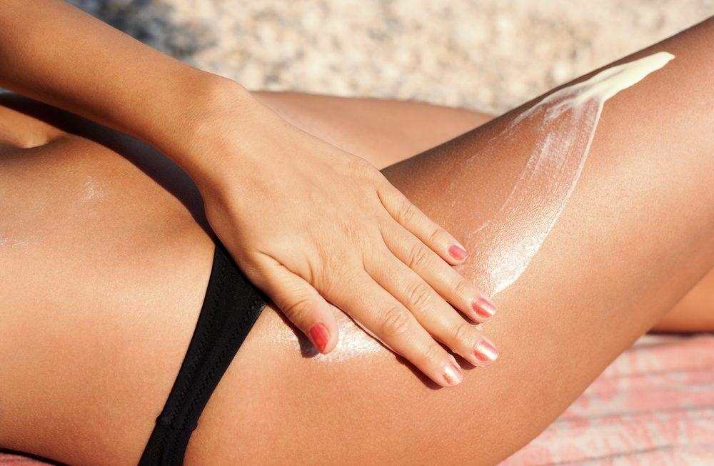 woman applying sunscreen to her leg