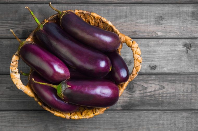 Fresh raw Purple Eggplant in a special wicker basket for Eggplant on gray wooden background. Top view, blank space.