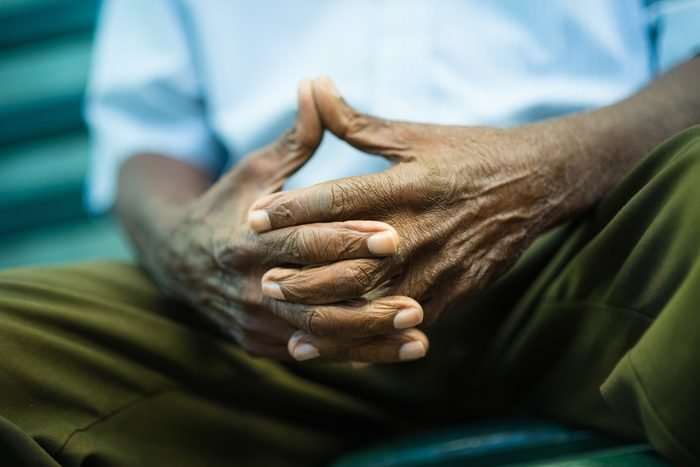 closeup of hands of elderly african american man sitting on bench