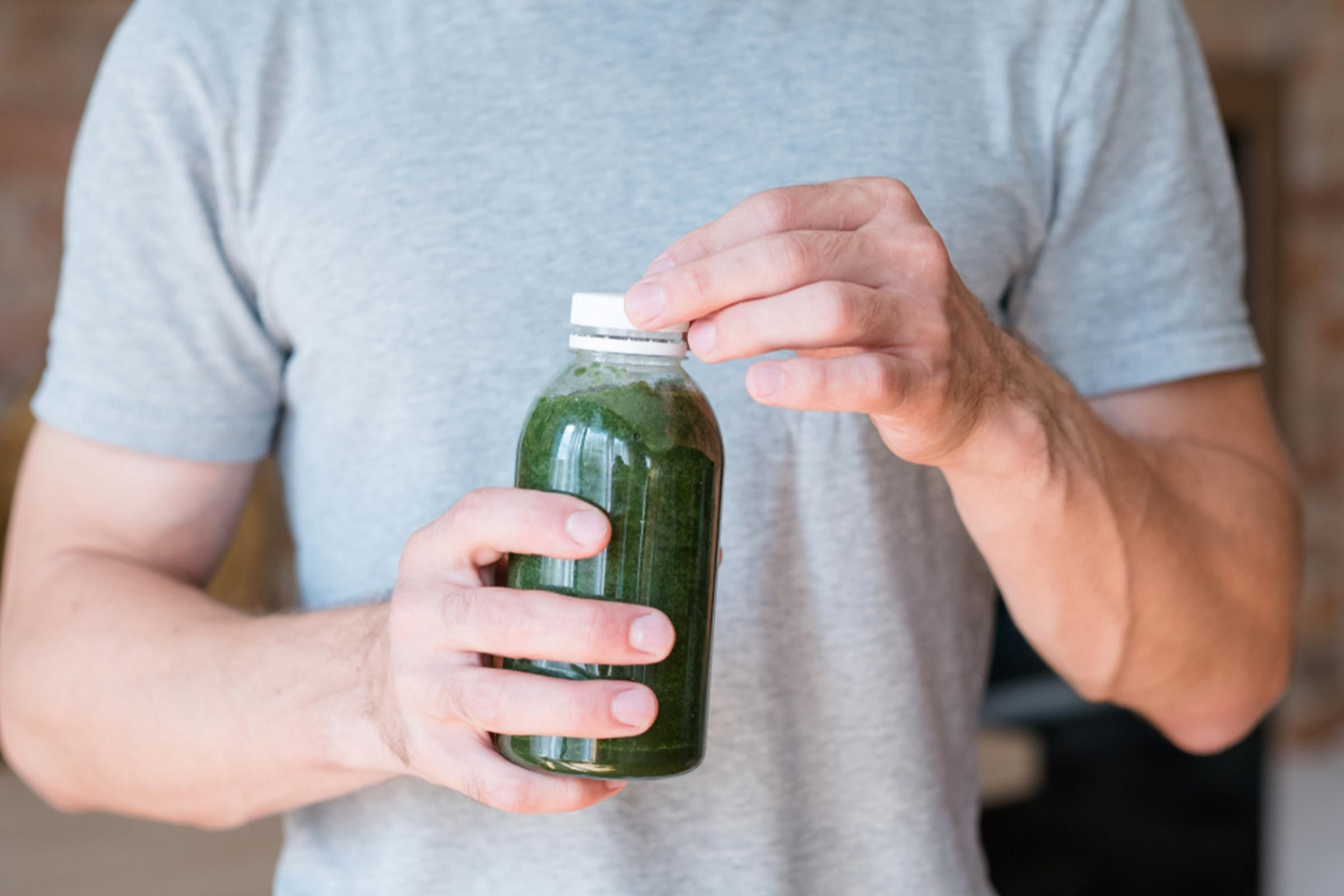 man holding green smoothie in a bottle