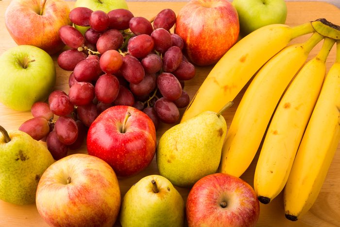 Closeup of fresh bananas, pears, apples and grapes on a wood table