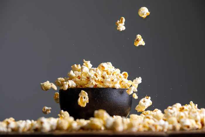 popped popcorn in a bowl and scattered on a table