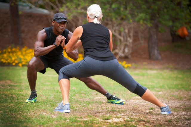 exercise trainer and woman exercising outside