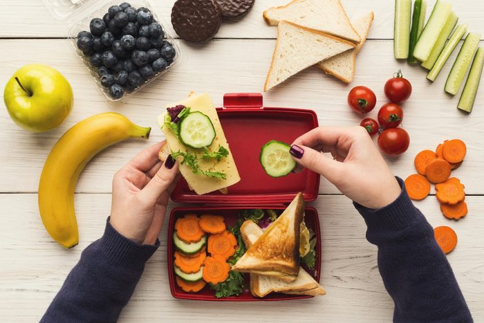 Preparing healthy vegetarian snacks on white rustic wood. Female hands making sandwiches and putting into take away plastic lunch box, top view.