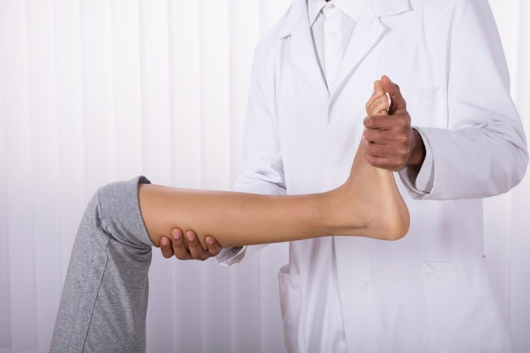 Woman doing leg and knee exercises with a doctor.
