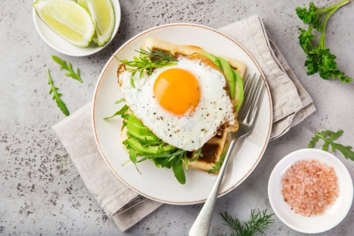 savory waffles with avocado, arugula and fried egg for breakfast, top view