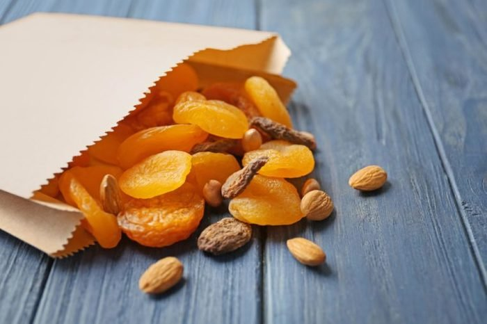 Paper bag with dried apricots and nuts on wooden background