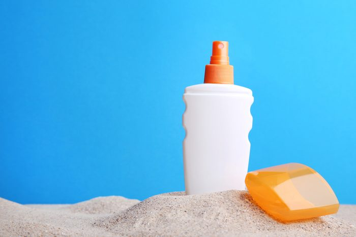 sunscreen bottle propped in sand