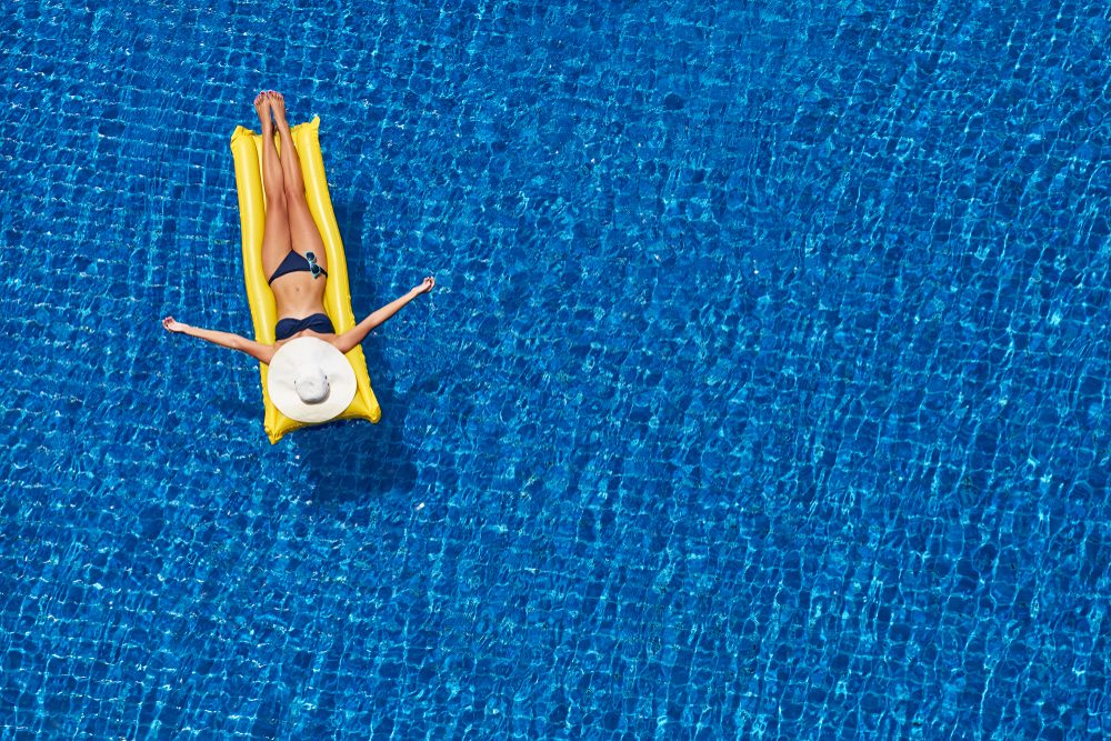 woman floating in pool on an inflatable raft