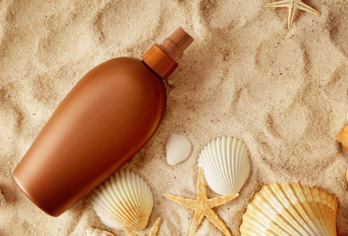 tanning lotion in sand with shells