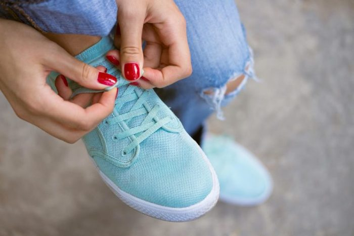 Female hands with a red manicure knotted laces on sports shoes. Young woman in blue jeans walking outdoors when she untied shoelace. A walk in the city.