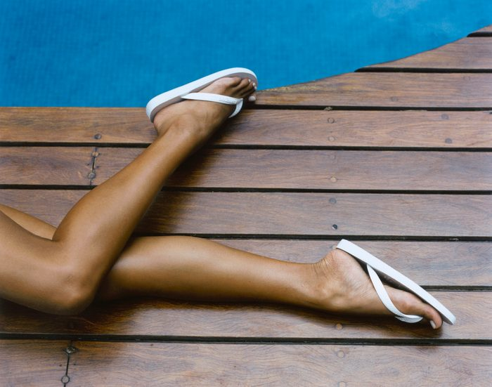 cropped shot of woman's legs on pool deck
