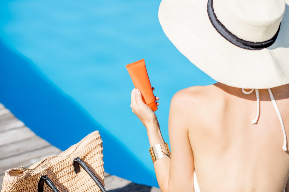 Woman in sun hat sitting with sunscreen near blue water